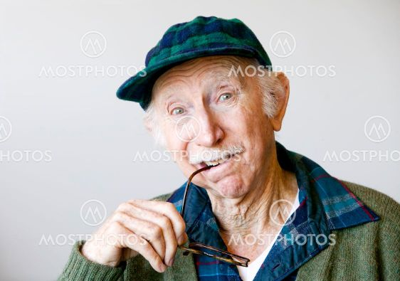 Thoughtful Senior Man in a Hat and Glasses