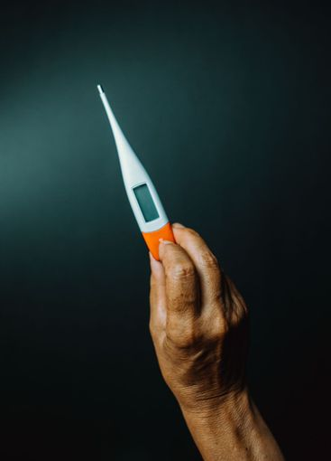 An old hand grabbing a thermometer over a dark background