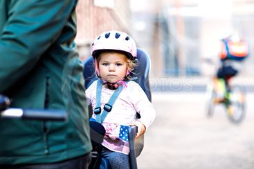Portrait of little toddler girl with security helmet on...