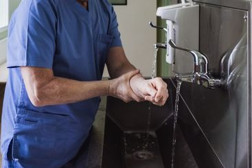 The doctor washes his hands under the tap in a stainless...