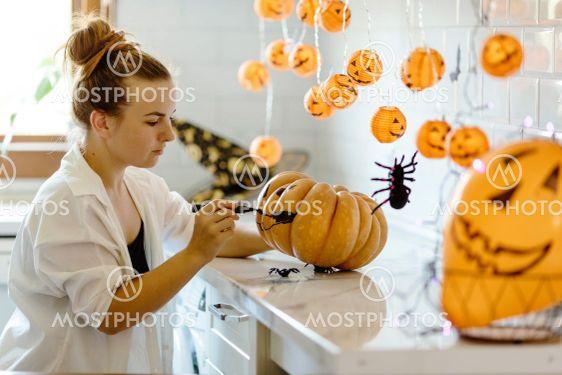 Woman paints face on orange pumpkin for Halloween....