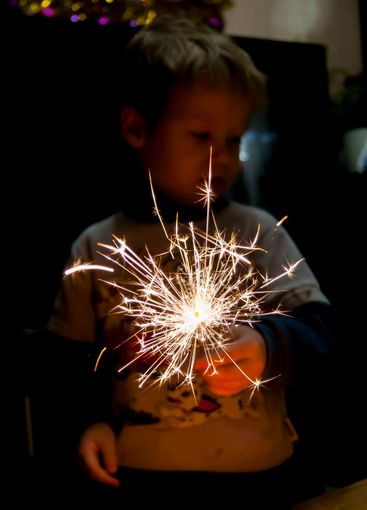 Burning Bengali fire on a dark background in a child's hand