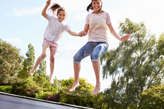 Mother And Daughter Bouncing On Trampoline Together