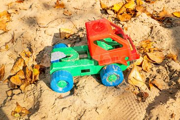 Children's plastic toy lorry in the sand.