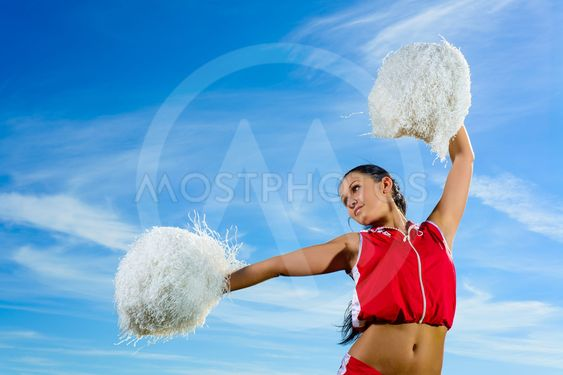 Young cheerleader in red costume with pampon