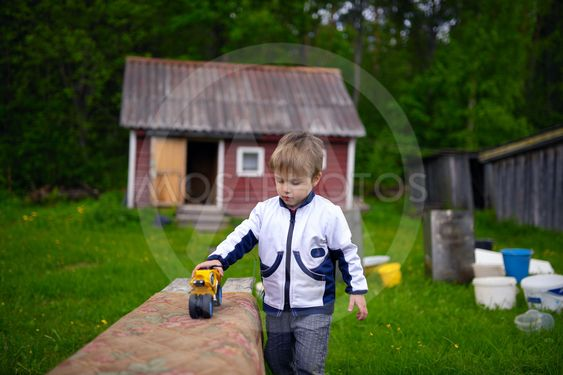 Little boy playing in toy bike in typical Russian village