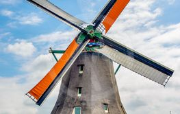 Tall windmill behind single story farmhouse