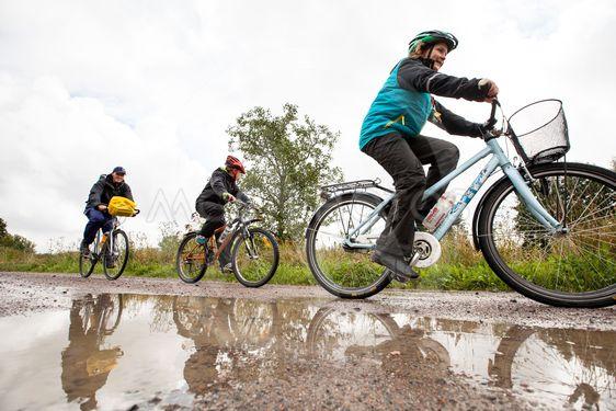 familj cyklar längs regnig grusväg