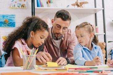 teacher in eyeglasses helping multicultural preschoolers...