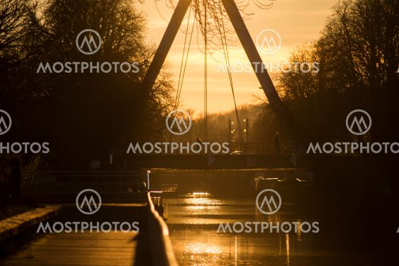 panorama with silhouette of suspended bridge and people...