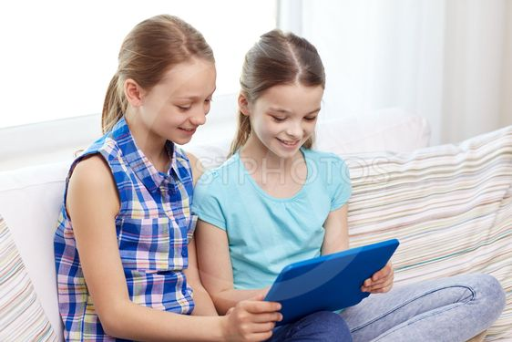 happy girls with tablet pc sitting on sofa at home