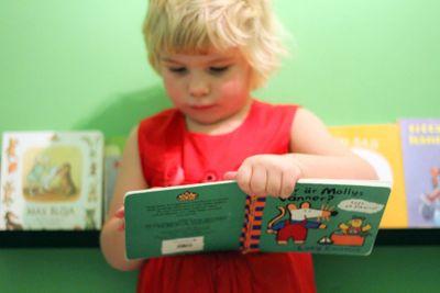 Liten flicka bläddrar i barnbok 2