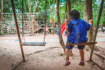 The boy wearing a blue shirt sitting in the swing