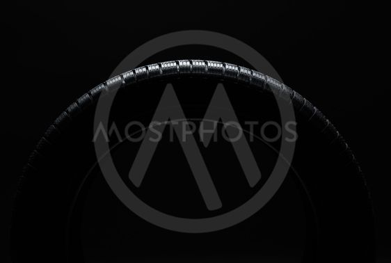 Tire over black background