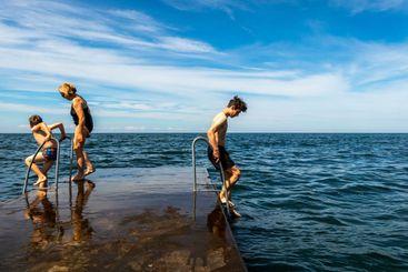 Familj som badar från stenbrygga vid havet Gotland.