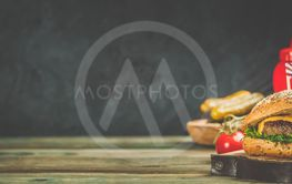 Homemade hamburgers on wooden background, space for text