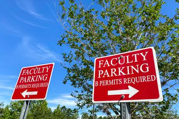 A faculty parking sign in a parking lot