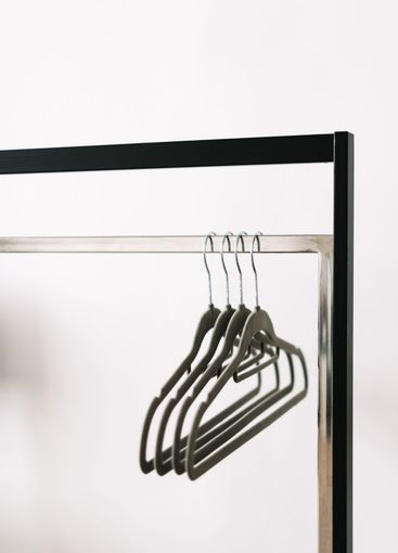 Black metal clothing rail with empty coat hangers in a...