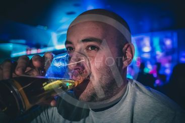 Young man drinking beer in a bar.