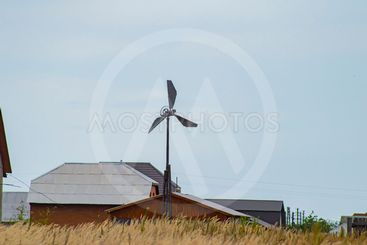 A wind electric generator near a house on the horizon.