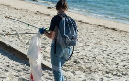 girl cleaning beach with plastic bag