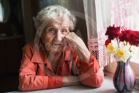 Portrait of elderly woman near window in the house.