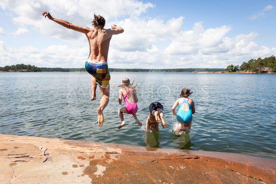 Pojke springer ut i vattnet och badar