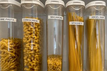 An organized pantry shelf with various types of pasta