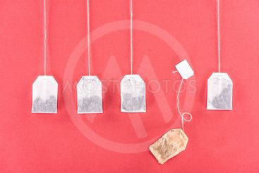 top view of four unused tea bags and one used tea bag...