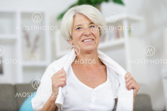 senior woman with a towel around her neck smiling