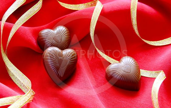 Chocolate hearts and gold ribbon on a red background.