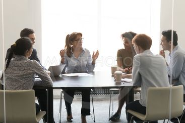 Middle-aged businesswoman speaking at diverse group...