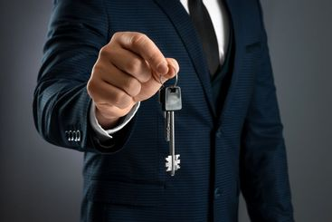 A man in a business suit holds out the keys in his hand....