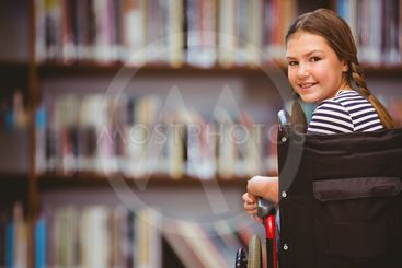 Composite image of girl sitting in wheelchair in school