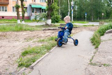 Blond-haired boy in blue rides a small tricycle on a...