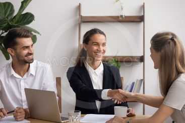 Smiling HR agent shaking hand congratulating candidate...