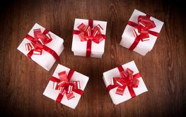 five white festive gift boxes with red bows on a wooden...