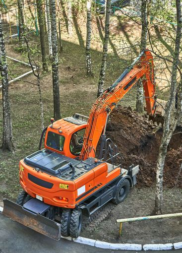 Mini excavator digging a trench among the trees for...