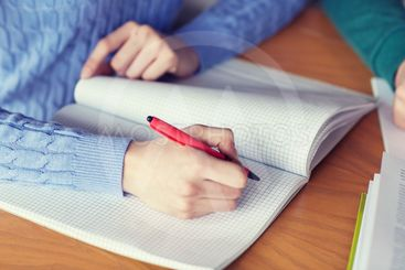 close up of student hands writing to notebook