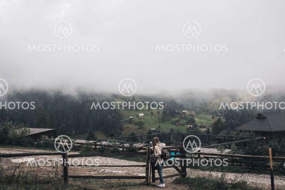 woman traveler near old fence against Carpathian...