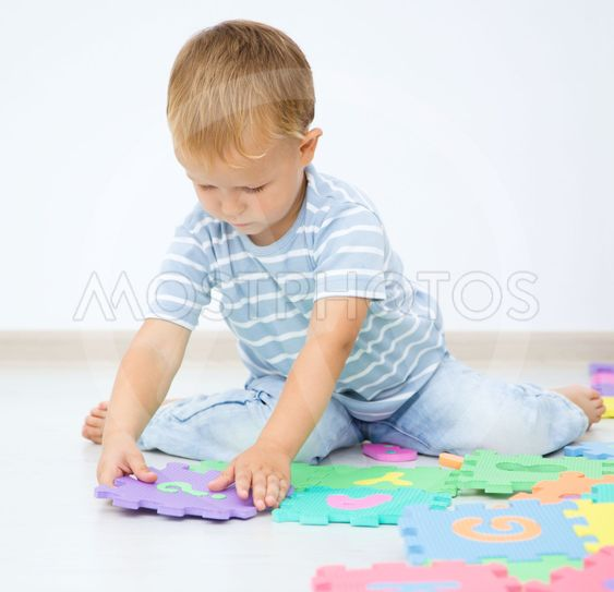 Little boy is putting together a big puzzle