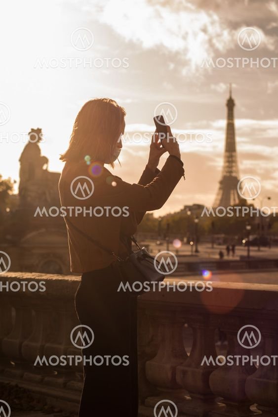 touristtaking a picture with her smartphone by sunset...