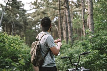 Young man with backpack cycling on a forest path, active...