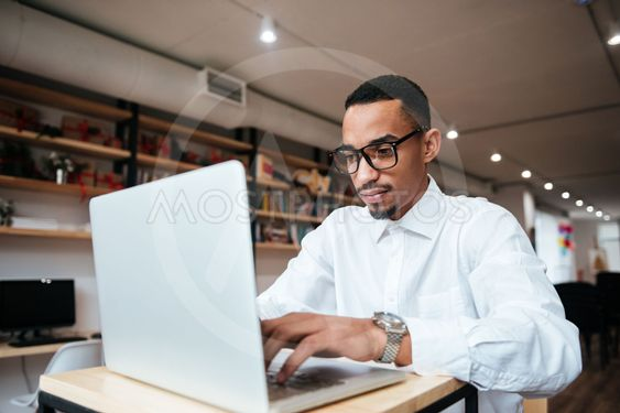 Handsome african businessman typing by laptop computer.