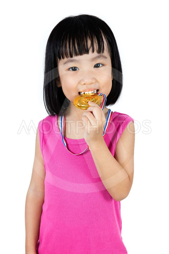 Asian Chinese little girl biting gold medal