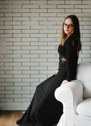 Woman sitting on white leather sofa. Concept of beauty...
