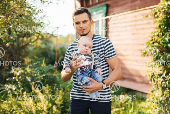 Happy young Caucasian dad with newborn son boy in hands