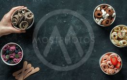 rolled ice creams in cone cups on dark background