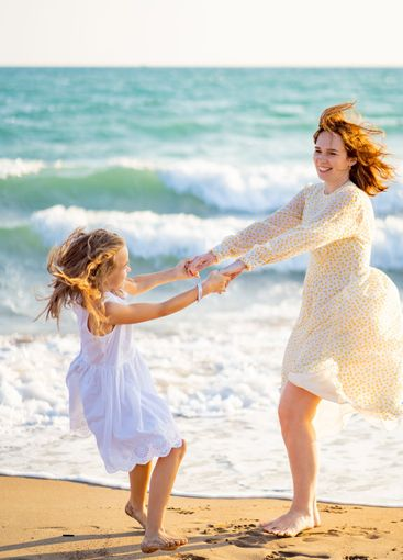 mom and kid walking on sea beach with big waves in windy...