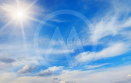 Sun and white clouds in blue sky